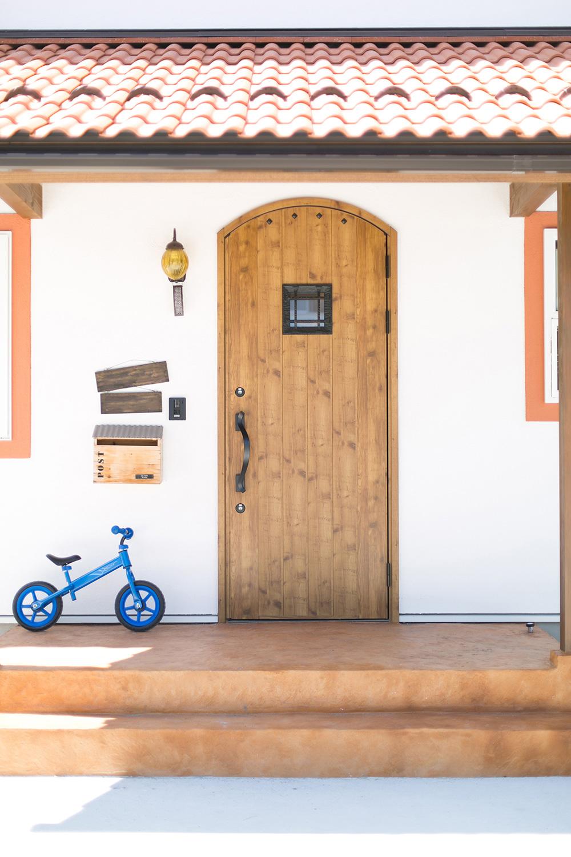 玄関ドアの可愛いお家。アーチのドアとおしゃれなポスト。