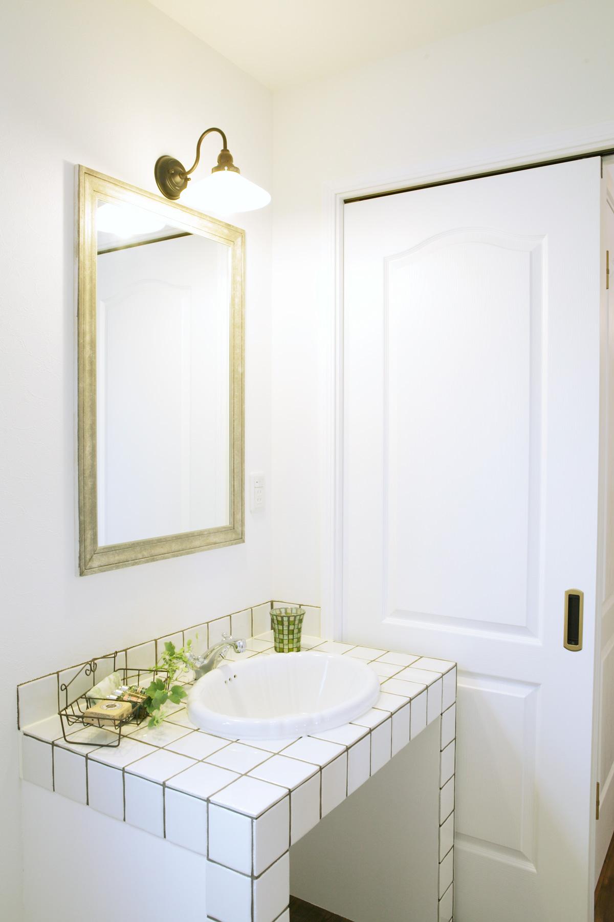 白を基調にした大きめのタイルがフレンチ風な洗面台